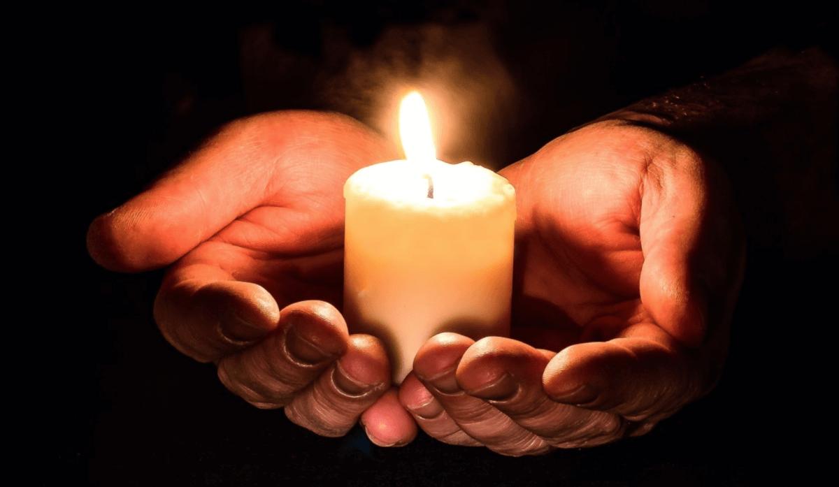 Bøn for klimaet Bedende hænder med lys
